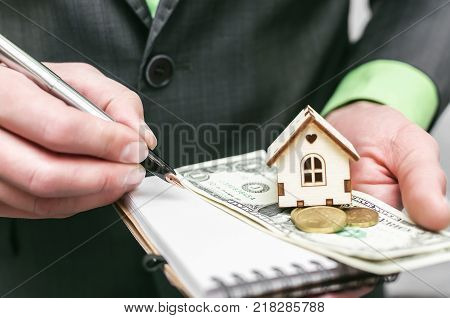 Small toy house home in the hands of real estate agent. Insurance agent.