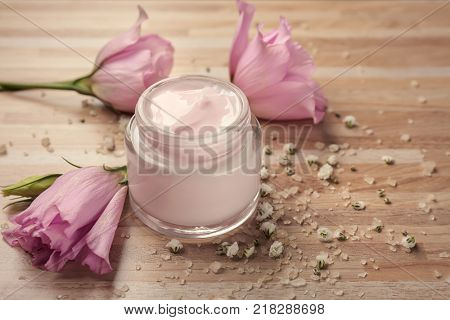 Jar of body cream and flowers on wooden background
