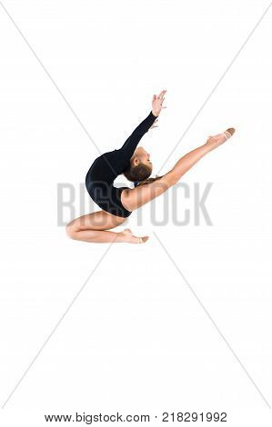 Yong gymnast in black tricot is jumping on isolated background