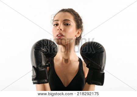 Pretty curly brunette fitness woman in boxing gloves looking at the camera over whit background