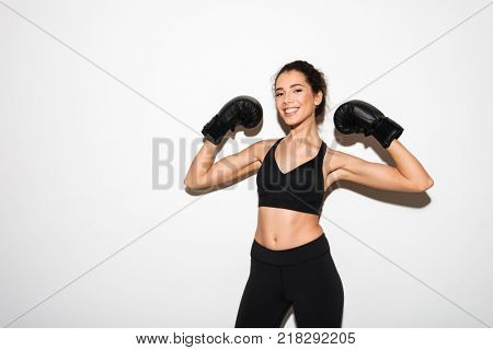 Smiling curly brunette fitness woman in boxing gloves showing her biceps while looking at the camera over white background