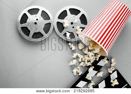Composition with popcorn, movie clapper and cinema film on grey background