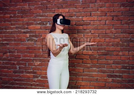 Virtual reality device. Woman playing game in virtual reality glasses. Headset with virtual screen. Girl touch something using modern glasses with virtual screen.