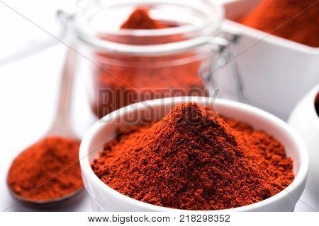 Red Chilly Powder in a bowl with dried red chillies over colourful background or pile of red chilli powder over plain background