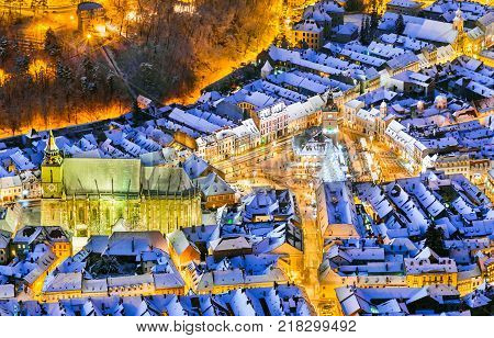 Brasov, Romania. Aerial view of the medieval city main square covered in snow with Christmas market and Xmas Tree, Transylvania, Eastern Europe.