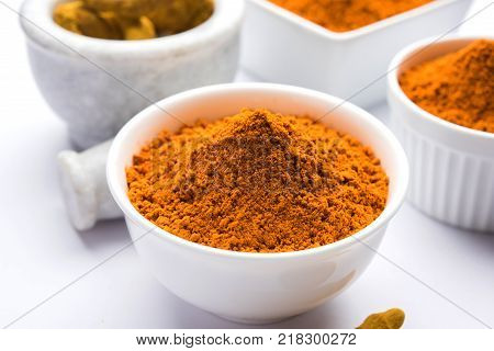 Turmeric powder in ceramic bowl with raw dried turmeric over plain background