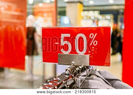Sale 50 percent off letters on red banner inside popular fashion store with blurred mall background. Discount and sale time in shops concept