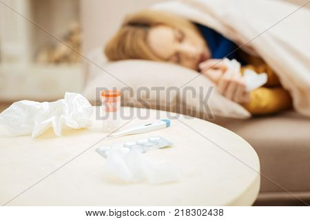 Taking a nap. Sick young blond woman feeling under the weather and sleeping on bed and a table with napkins and medications standing in front of the couch