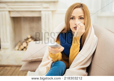 Sick leave. Beautiful cheerless young dark-eyed woman having runny nose and feeling unwell and sitting on the couch and holding remote control