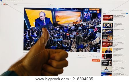 PARIS FRANCE - DEC 14 2017: Man thumb up for the Russian President - watching on Youtube live channel of Rossiya RTR the Russian President Vladimir Putin give final media Q&A before March election