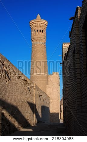 View from the west side on Kalyan minaret. The minaret designed by Bako was built in 1127. This minaret also known as the Tower of Death is one of the most prominent landmarks in the Bukhara Uzbekistan.