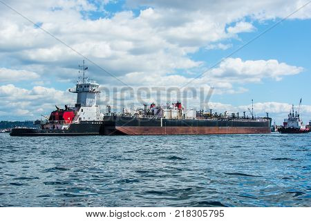 Tug inserted in notch in stern of barge with assist from separate tug.