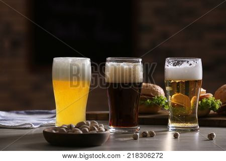 Glasses with different sorts of beer on table in sport bar