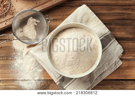 Ceramic bowl and sieve with buckwheat flour on table