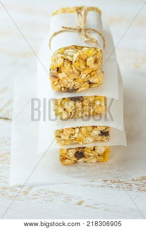 Stacked Homemade Granola Muesli Cereal Bars with Oats Nuts Raisins Honey Dried Apples. Lined with Parchment Paper Tied with Twine. White Wood Background. Healthy Vegetarian Snack.