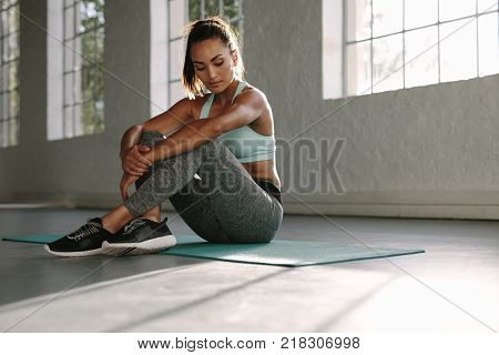 Woman resting in between workouts. Healthy young female resting after training in gym.