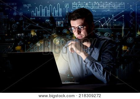 Young handsome businessman working late at night in the office with blue calculations in the background