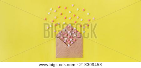 Multicolor sweets sugar candy hearts fly out of craft paper envelope on the bright yellow background . Valentine day. love concept. Gift message for lover. Space for text. Wide banner