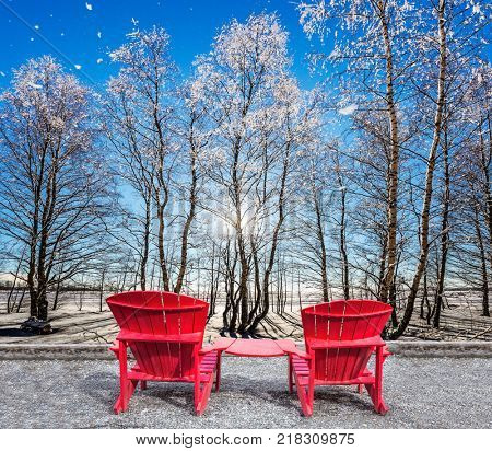 Winter frosty day. Large and comfortable red plastic chaise lounges for relaxing. Sunset in the Arctic. The concept of extreme and ecotourism tourism