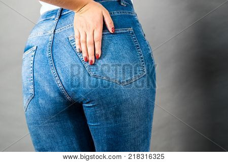 Closeup of female plus size hips buttocks wearing blue jeans woman presenting fashionable outfit. Fashion clothing femininity concept. Gray background