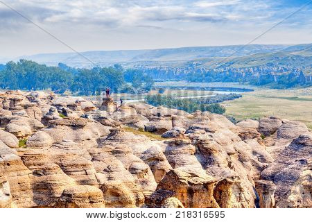 LETHBRIDGE CANADA - AUG 22 2016: Visitors pose for pictures on top of the hoodoos at Writing-on-Stone Provincial Park in Alberta Canada.