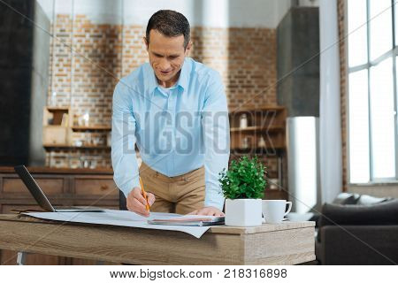 Using all devises. Cheerful male person looking downwards while drawing project work, leaning on table