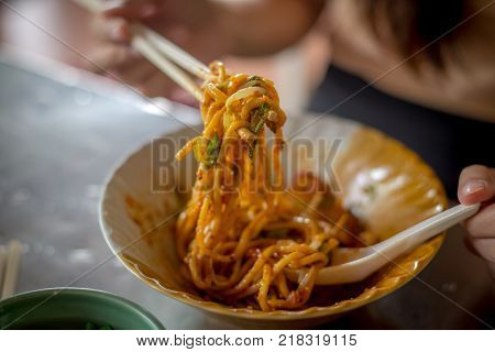 Fried Hokkien Noodles tong by chopsticks ready to eat in the southern of Thailand Phuket local Food