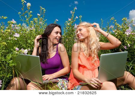 Two beautiful girl with laptop computer in outdoors on green grass