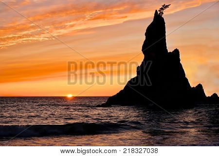Sunset at Rialto Beach. Sea stack silhouette by sunset sky. Pacific Northwest. Olympic National Park on Olympic Penincula near Olympica and Port Angeles. Seattle. Washington. United States of America.