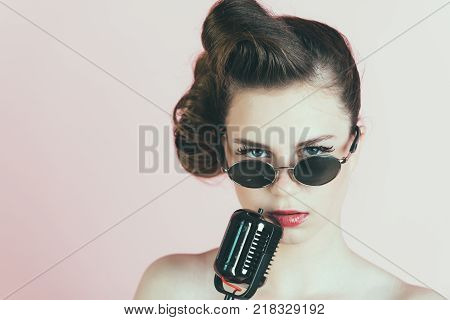 singer girl in glasses on pink background with retro hair and fashionable makeup beauty and fashion pinup music and karaoke dj poster