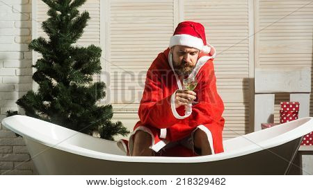 Expectation love and betrayal. Winter holiday and xmas party. Home alone bad santa in bath. Christmas man with beard waiting. Hipster santa at Christmas tree drink wine loneliness.