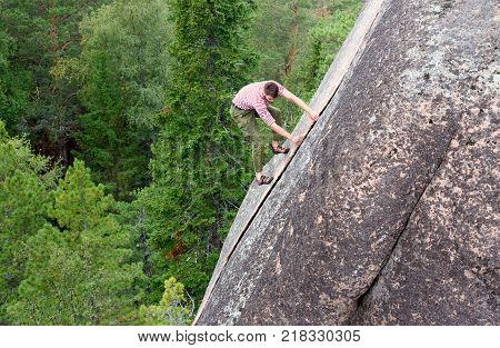 Krasnoyarsk Russia- August 10 2017: Unidentified Climber climbs on the rock wall. Pillar the Fourth. Central pillars of Russian reserve Stolby Nature Sanctuary