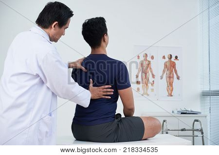 Doctor checking spine of a young man within the annual medical examination