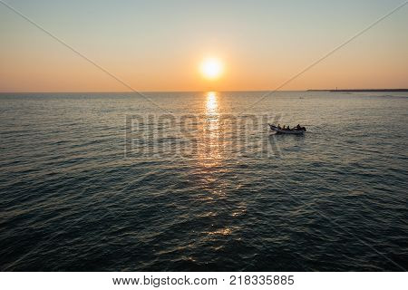 Old vintage fishing netting boat with oars men rowing to cast nets morning dawn ocean horizon landscape