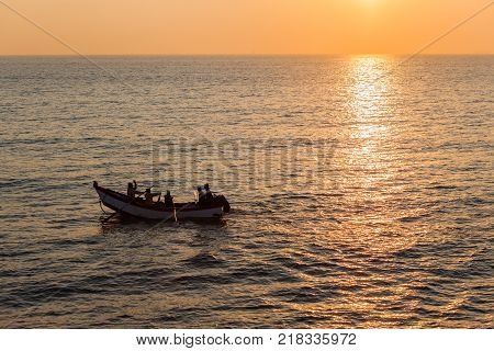 Old vintage fishing netting boat with men rowing oars morning dawn ocean horizon landscape