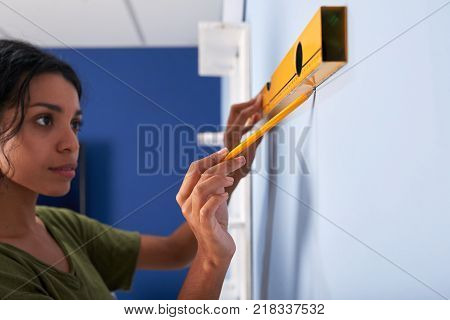 Pretty Hispanic woman using construction level to draw a stright line on the wall