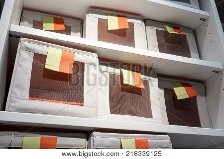 Fabric Storage Boxes In Square Shape With Orange And Yellow Pull To Open Tag Arranged On White Shelf