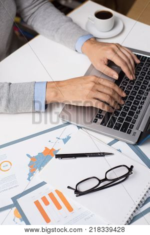 Businesswoman working with laptop in office. Close-up of female hands typing on modern computer at desk with messy papers. Analyst concept