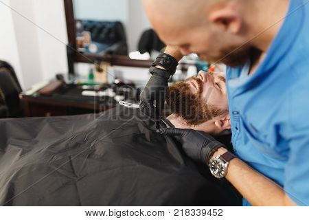 Close Up Of Male Professional Hairdresser Serving Client By Clipper. Ginger Handsome Stylish Young M