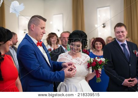 Belarus Gomel September 29 2017 Wedding Feast.The bride and the groom in the registry office .Registration of marriage. The groom wears the bride's ring