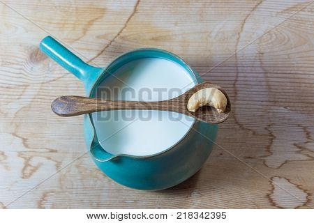 Handmade ceramic pitcher of cashew milk centered vintage wood background wooden spoon with a single cashew horizontal aspect
