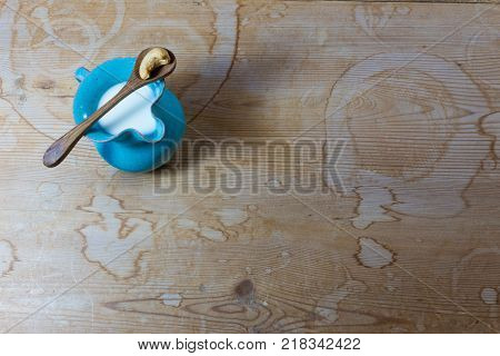 Very small blue ceramic pitcher of cashew milk wooden spoon with single cashew wood background copy space horizontal aspect