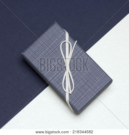 Close-up of gift box wrapped in elegant style with dark blue and milk colors. Stylish packing for watches and jewelry