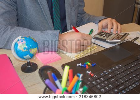 Businessman using a calculator to calculate the numbers. Businessman calculate finance and thinking about problem in home office. Administrator using a calculator to calculate the numbers
