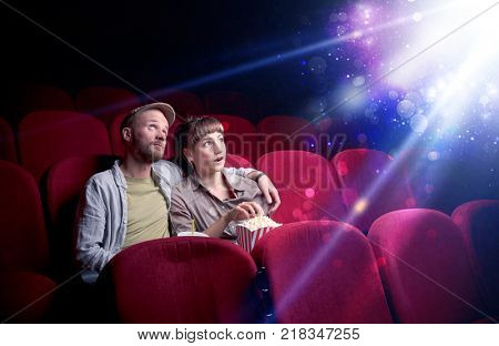 Romantic couple cuddling and watching the miraculous part of the film poster
