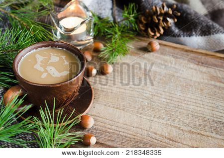 Cozy Christmas evening at home. Hot cocoa warm pleid and candle with branches of pine on wooden table. Christmas winter and holiday concept. Rustic life.