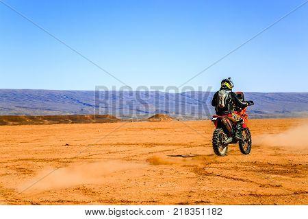 Ait Saoun Morocco - February 22 2016: Rare view of man in helmet riding bike in Ait Saoun desert of Morocco.