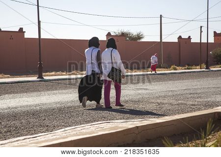 Ait Saoun Morocco - February 23 2016: Two unidentified women in conversation and talking while walking on streets of Ait Saoun village in Morocco.