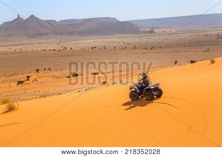 Merzouga Morocco - February 26 2016: Unidentified person and pilot riding a RZR800 in Merzounga desert in Morocco. Merzouga is famous for its dunes the highest in Morocco.