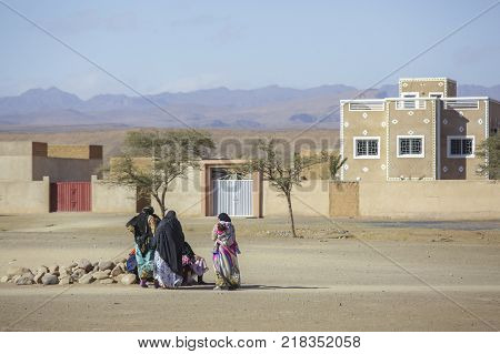 Tinghir Morocco - February 27 2016: Women sitting outside sand house on rocks talking to each other in Tinghur city of southern Morocco. Tinghir city is at the center of one of the most attractive oases in southern Morocco.